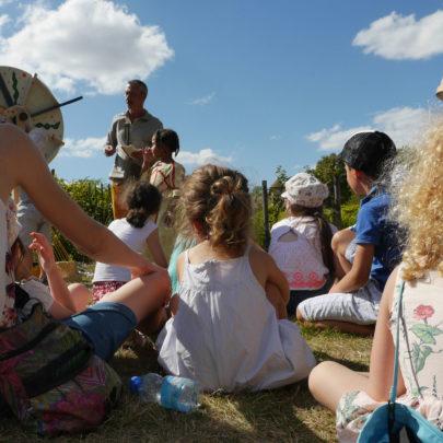 Groupes d'enfants assistant à un spectacle dans le jardin